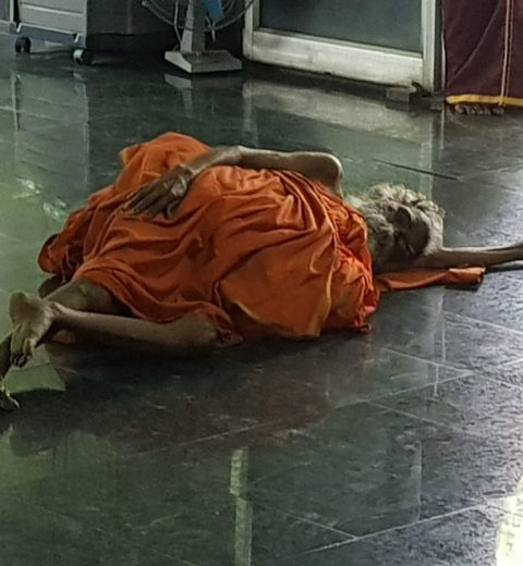 muoku podi swami laying on floor in meditation hall at sheshadri ashram