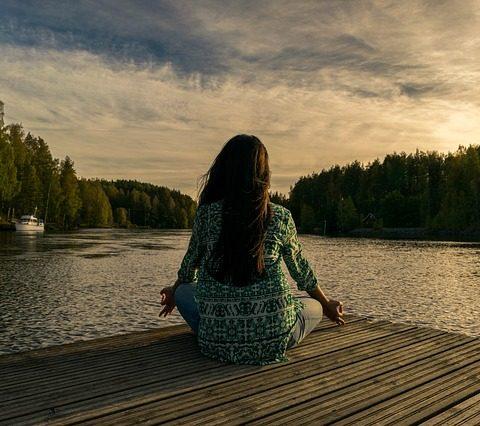 woman in meditation at lake